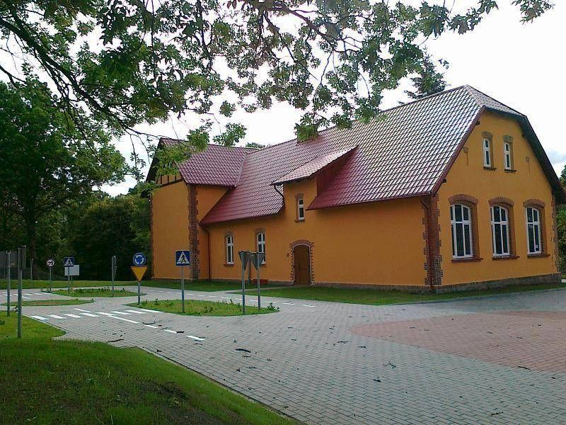 Pomarańczowy budynek z czerwonym dachem